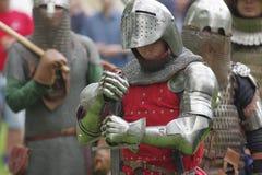 Knight в стальном панцыре, держа шпагу рук в бое Стоковые Изображения