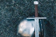 Knight& x27; шлем s и сияющий металл лежа на том основании, оно положил старую стальную шпагу с кожаной ручкой Стоковое фото RF