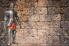 Knight against ancient stone wall Stock Photography