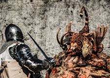 Knight and dragon. Armoured warrior fighting with a chimera monster. Poster on the grunge background Stock Image
