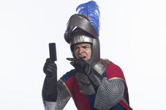 Knight annoyed with smartphone, horizontal Royalty Free Stock Photo