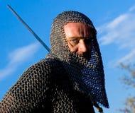 Knight a armadura desgastando e prenda-a em uma espada imagens de stock