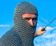 Knight a armadura desgastando e prenda-a em uma espada imagem de stock royalty free