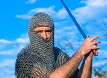 Knight a armadura desgastando e prenda-a em uma espada fotos de stock