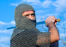Knight a armadura desgastando e prenda-a em uma espada fotografia de stock