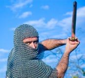 Knight a armadura desgastando e prenda-a em uma espada foto de stock royalty free
