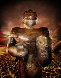 Knight in armor. A knight in armor with glowing eyes and a desolate charred smoking background. A war concept royalty free stock image
