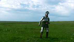 Knight in armor with a sword. Medieval knight in armor, and with an open visor exercise with a sword against the backdrop of steppe grass and blue sky stock video