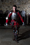 Knight in Armor With Sword Standing in Old Church and Looking at Camera Stock Photo