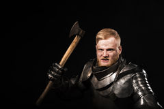 Knight in armour with axe on the black background Royalty Free Stock Image