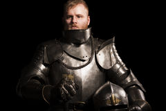 Knight in armour after battle on the black background. Tired knight after the battle. Close up Royalty Free Stock Image