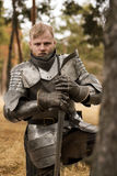 Knight in armour before battle on forest background. Knight before battle. Close up Royalty Free Stock Photo