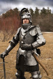 Knight in armour after battle on forest background. Knight before battle. Close up. Win battle Royalty Free Stock Photography