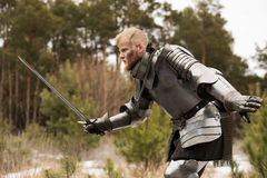 Knight in armour during battle on forest background Royalty Free Stock Photography