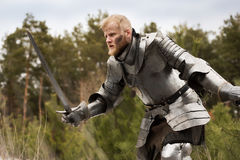 Knight in armour during battle on forest background Stock Photo