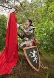 Knight in armour and maid. In forest Stock Image