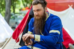 Knight with a beard in a blue traditional suit sits in front of the tent and plays an old dice game. Nis, Serbia - June 15. 2019: Knight with a beard in a blue stock photography