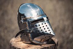 Knight, a brilliant helmet standing on a wooden stump. Close-up Royalty Free Stock Image