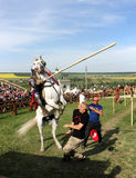 Knight on bucking horse. KHOTYN - MAY 10: Knight with lance riding a bucking horse during Festival Medieval Khotyn on May 10, 2013, Ukraine Royalty Free Stock Images