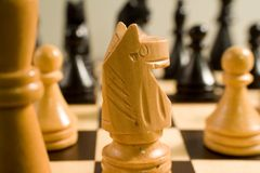 Knight on the chessboard. Chess set and the knight at the first plan Royalty Free Stock Photo