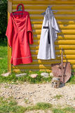 Knight cloak and dress on wooden wall Royalty Free Stock Photos