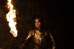 Knight com uma tocha e uma espada na noite em um fundo da parede imagens de stock