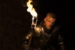 Knight com uma tocha na noite em um fundo da parede imagens de stock
