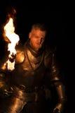 Knight com uma tocha na noite em um fundo da parede foto de stock royalty free