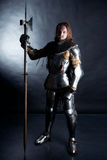 Knight on dark background. A medieval warrior in armor with a halberd. Knight on dark background Stock Image