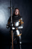 Knight on dark background. A medieval warrior in armor with a halberd. Knight on dark background Royalty Free Stock Image