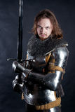 Knight on dark background. A medieval warrior in armor with a sword. Knight on dark background Stock Images