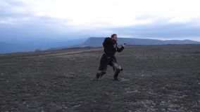 Knight fencing his sword against the backdrop of the mountains at morning. Knight fencing his sword against the backdrop of the mountains at sunset Slow motion stock video