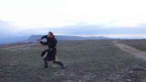 Knight fencing his sword against the backdrop of the mountains at sunset. Slow motion video stock video
