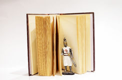 Knight figure coming from old open book Stock Image