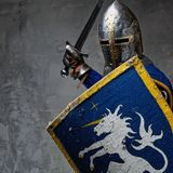 Knight in a full armor. Medieval knight in attack position Royalty Free Stock Photo