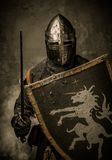 Knight in full armour. Medieval knight with sword and shield against stone wall Royalty Free Stock Photo