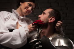 Knight giving a rose to lady. Closeup portrait of medieval knight giving red rose to beautiful romantic brunette lady sitting on his knee, on dark stone Royalty Free Stock Photos