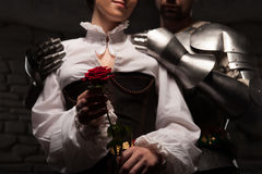 Knight giving a rose to lady. Closeup portrait of red rose, medieval knight embracing beautiful romantic brunette lady from behind, on dark stone background Stock Image