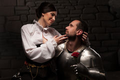 Knight giving a rose to lady. Full length portrait of couple in historical costumes, medieval knight giving rose to beautiful brunette lady sitting on his knee Stock Images
