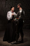 Knight giving a rose to lady. Full length portrait of a couple in historical costumes, medieval knight giving rose to beautiful romantic brunette lady, on dark Stock Photo