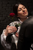 Knight giving a rose to lady. Medieval knight from behind giving rose to a beautiful romantic brunette lady, on dark stone wall background Stock Image