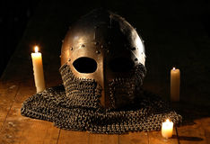 Knight Helmet. Ancient knight helmet with hauberk near candles on wooden background Royalty Free Stock Image