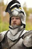 Knight in helmet and armour before battle on forest background. Knight before battle. Close up Stock Photo