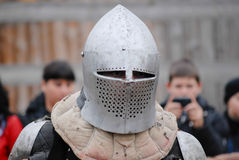 Knight in helmet before festival battle with spectators Stock Photos