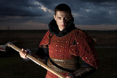 Knight holding axe. On a sky background Royalty Free Stock Photography