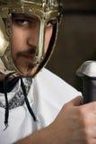 Knight holding his sword and looking at camera. Knight with gold helmet holding his sword and looking at camera Stock Photos