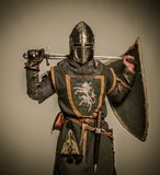 Knight holding sword behind his back. Medieval knight with a sword Stock Images
