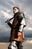 Knight holding sword. On a sky background Royalty Free Stock Photo
