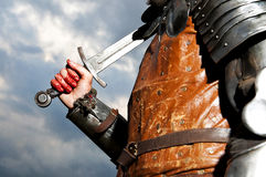 Knight holding sword on a sky background Royalty Free Stock Photography
