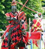 Knight on horseback. The red knight of old                       on horse back jousting in full armour Royalty Free Stock Photos